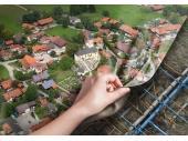 Hand deckt Luftbild auf und gibt den Blick auf das Rohrnetz unter der Erdoberfläche frei.